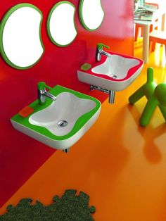 A childrens bathroom with colorful accents and fun sinks and mirrors