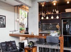 Nesta cozinha supermoderna, os pendentes foram feitos apenas com as lâmpadas bem redondas, combinando com toda a elegância da mesa de madeira e dos móveis escuros. Saiba mais no nosso blog.