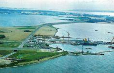 Farø blev landfast med Bogø i 1979 ved en dæmning med en 8 m bred landevej. Foto fra 1979. Dæmningen består af indpumpet sand, tilsået med græssorter, der tåler havvand. Skråningerne er flade og uden stensikring, så de på naturlig måde indgår i landskabet. Arbejdet begyndte i starten af 1978 og omfattede også jord- og vejarbejder på Farø for den kommende bro. Bemærk den store arbejdshavn på Farø. Den blev fjernet efter byggeriets afslutning. Kilde: Farøbroerne. Scan efter foto af Lene Storm.