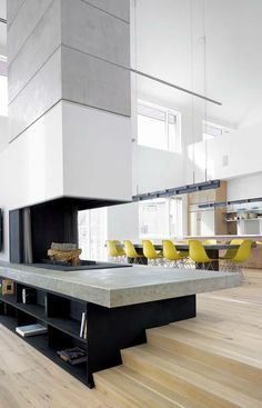 TALL ORDER: The expansive double-height living room and kitchen in this ontario ski-country chalet were conceived by Toronto's atelier kastelic buffey as a mostly neutral backdrop for darker tones and colourful accents. Designed by the studio, the limestone and cold-rolled steel hearth bridges the two rooms. Yellow fibreglass eames chairs and oak cabinetry lend warmth and interest to the kitchen.