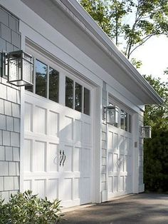 Exterior - These garage doors repeat the recessed square panels found throughout the home. The glass panels above provide some light into the garage during the day. Three simple lamp fixtures provide ample illumination and beauty to this area of the home exterior. #bhg.com: