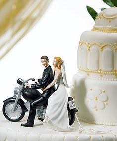 """This romantic wedding couple are seated on a classic motor bike that has been magnificently crafted and includes a miniature """"Just Married"""" license plate along with actual paper pom poms delicately tied to the back fender. Hand painted porcelain."""