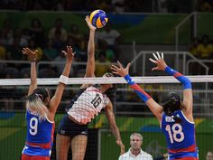Team USA middle blocker Foluke Akinradewo (16) plays the ball to Puerto Rico weak side hitter Aurea Cruz (9) and middle blocker Lynda Morales (18) during a match in the preliminary round in the Rio 2016 Summer Olympic Games at Maracanazinho.  Kirby Lee-USA TODAY Sports