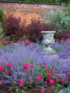 Lavender in lilac glory, fuschia flowers giving a pop of glorious color, a beautiful weathered urn in the midst of a garden utopia ... Exquisite!