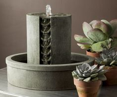 Mini Series Coin Fountain    This tabletop fountain will add a spa-like quality to your indoor or outdoor decor at home. The peaceful sound of running water will create a relaxing atmosphere for you, your friends and family to enjoy. Cast stone fountains from Campania International are designed to last a lifetime and come in 12 finish colors. Shown in Alpine Stone.