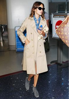 Alexa Chung wears a denim romper, khaki trench coat, cat-eye sunglasses, and gray suede ankle boots