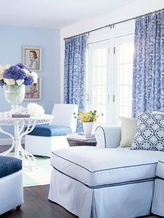 This simplistic monochromatic blue color scheme is drenched in blue from the pale blue wall color to the blue curtains, cushons, and flowers