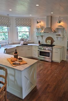 White kitchen with thunder white granite countertops & white subway tile.The white is relieved a bit by the wood floors & the grey in the stainless & fabric. I would want upper cabinets, but this is the style is popular now. It works if you have a pantry.