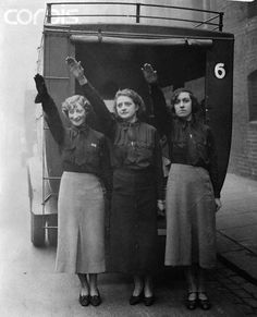Three female blackshirts, members of the British Union of Fascists, salute as they leave their Chelsea headquarters for Birmingham, where they will attend a meeting addressed by their leader, Oswald Mosley. 1934
