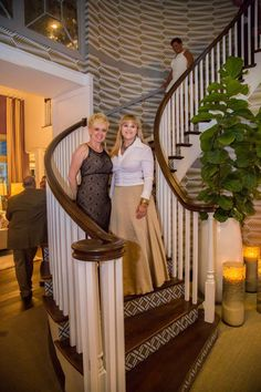 The evening of the Designer House Preview Gala, designers of the entrance hall and stair area, the Bridget Beari team, Rachel Tate Parrish, assistant, and Susan Jamieson, principal, stand on the grand staircase in front of their glorious wallpaper in the 2014 Richmond Symphony Orchestra League Designer House, Hampton Manor, built by Richmond luxury home builder, Bel Arbor Builders, at Hallsley, in Midlothian, VA!  Photo by East West Communities photographer