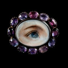 """Circa 1825 """"Lover's Eye"""" Pin with Hair Locket Back. This is a gorgeous example of a lover's eye, with the painted eye framed in foiled amethyst. Made of 12 karat rose gold and fitted with an original locket back, the original braided strand of hair is still immaculately intact under glass. 1.25 x 1 inch"""