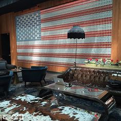 Blogger Jen @girlwithahotspot is working at Dream Hotels @dreamhotels surrounded by an inspirational wall -- an American flag constructed from Tecate @tecate_cerveza beer cans -- in New York NY #workhardanywhere