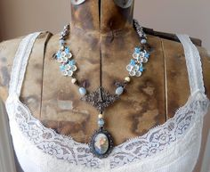 Hand painted portrait necklace features an eclectic assemblage of vintage and antique elements to create this beautiful feminine and unique piece. The focal point is a gorgeous hand painted portrait cameo brooch featuring a miniature reproduction of the famous Madonna Delle Rocce painting by Fillipo Lippi. She is surrounded by an antique filigree brooch frame made of hallmarked 800 European sterling silver. The brooch is suspended via a wire wrapped bone carved bead and aquamarine gemstone…