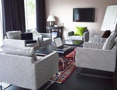 Seating area with grey armchairs and black-brown coffee tables