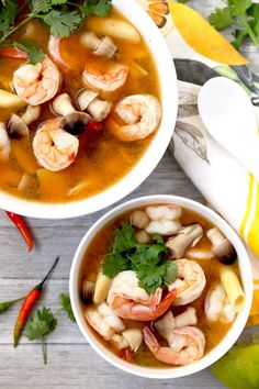 Overhead view of one large and one small bowl of Thai Tom Yum Soup on top of a white wooden surface. You can see small Thai chiles, cilantro springs next to the bowls. Thai Hot And Sour Soup, Sweet And Sour Soup, Thai Tom Yum Soup, Thai Soup, Clean Recipes, Soup Recipes, Cooking Recipes, Healthy Recipes, Thai Recipes