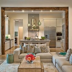 Living room + kitchen. I love the wood beam separating the two room