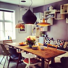 Scandi style dining room. Very eclectic. Mismatched chairs, cushions give colour, storage in arch over seating.