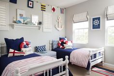 Blue sailor themed boys' bedroom features a pair of white poster beds dressed in red and blue bedding and lifesaver pillows placed below a shelf and a marcee anchor.