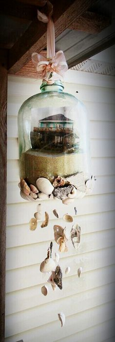 Sea shell wind chime made with an old glass jug, ribbon, fishing string and a hot glue gun