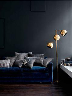 Blue velvet sofa and brass lamp