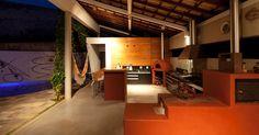 """O lado """"caipira"""" da Casa FP, projetada pelo arquiteto João Diniz, se traduz nesse varandão. Nele, a estrela é conjunto de equipamentos culinários como o fogão à lenha e o forno de barro. Destaque também para a cobertura de telhas coloniais. Lá fora, à esquerda, a piscina em semi-círculo e o painel cerâmico de Fernando Pacheco"""