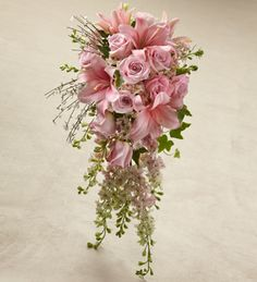 Pink roses, larkspur, and LA Hybrid Lilies are blushingly beautiful accented with white genista and variegated ivy. Tied together at the stems with a silver gray satin ribbon, this bouquet brings a sweet sophistication to your big day.