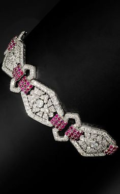 A ruby and diamond bracelet, circa 1935 The three pierced and articulated lozenge-shaped panels of floral and foliate design set with old brilliant and single-cut diamonds, connected by openwork double-chevrons and circular-cut ruby-set spacers, diamonds approximately 22.25 carats total, maker's mark for Goineau, French assay marks, length 17.5cm