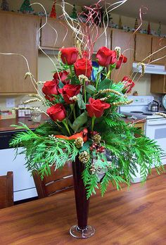 Three foot tall Holiday Floral Arrangement. Red roses, green cedar bows, floral fill, cones and a faux cardinal ... fit snuggly in a amazing 18 inch fluted red glass vase. COME SEE MY OTHER ARRANGEMENTS !!!