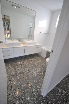 White bathroom with polished aggregate concrete floors. Image courtesy of Polished Concrete Design Floors