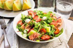 Recept voor zomerse salade voor 4 personen. Met zout, suiker, peper, serrano ham, mozzarella, galiameloen, aardbei, cherrytomaat, bosui, slamelange, balsamicodressing en munt