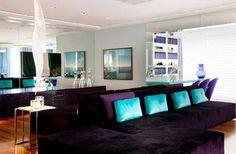 Cores na decoração - Sala de estar com espelho e almofadas azuis.