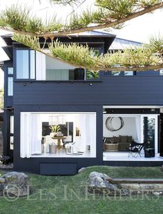"""This Sydney beach house is decorated with a beautiful minimalist style that proves that many times """"less is more"""". The navy blue exterior of this house is"""