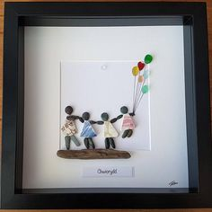 A beautiful and unique handmade beach pebble art picture of two sisters / best friends standing on driftwood holding balloons and being blown in the wind. This picture is a lovely home decoration and would make a perfect gift. The picture is made using pebbles and driftwood. All materials