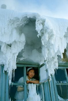 A woman gazes through a window surrounded by ice in Oymyakon, Siberia, in 1967. Photograph by Dean Conger, National Geographic
