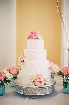 Wedding Cake Surrounded by Mason Jar Peony Posies - On SMP: http://www.StyleMePretty.com/southeast-weddings/2014/03/18/a-romantic-celebration-in-south-carolina/ Ashley Seawell Photography on #SMP