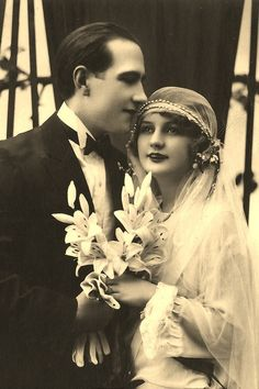 this picture is from the 1920s an shows a newlywed couple. wedding dresses looked different in the 1920s then they do today. the couple looks happy.in the 1920s people started to marry for love. before then, people got married for money.