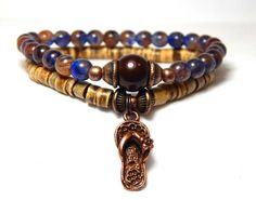 This beach themed stacked bracelet set is made with 6mm Dark Blue and Natural Swirled glass bracelet that features a Swarovski Pearl focal bead and a 5mm Light Coco Wood Bracelet with a Copper Flip Fl