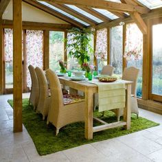 Conservatory dining room with beams    This conservatory dining room combines classic wicker chairs with a rustic dining table for a homely look. Pretty informal blinds to match the seat cushions add a splash of hot pink to the sunny space. A green table runner looks great with grass green tableware, and a matching rug defines the eating space.