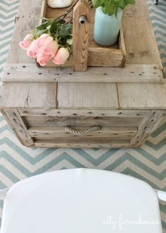 City Farmhouse vintage crate turned into outdoor coffee table with casters.