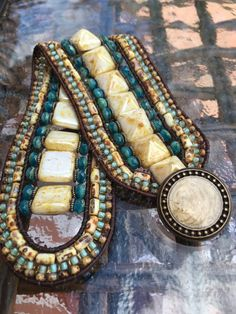 Beaded leather cuff bracelet with Czech pyramid beads, turquoise and neutral beads, and a antique brass button closure.
