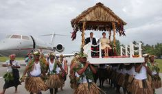 Britain's Prince William (L) and his wife Catherine (R), the Duchess of Cambridge, are carried on thrones upon their arrival at Funafuti in Tuvalu on September 18, 2012. Nearly half the population of 10,500 turned out to greet the future king and his wife, a day after their lawyers lodged a criminal complaint in Paris against a French magazine that published photos of Catherine sunbathing topless. AFP PHOTO / TONY PRCEVICH (Photo credit should read Tony Prcevich/AFP/GettyImages)