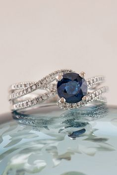Swirl engagement ring with a standout blue sapphire center stone. This is the one!