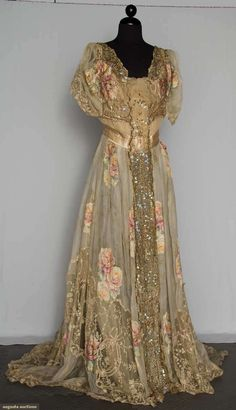 Evening gown, 1890-1920. 1 piece cream silk chiffon w/ pale printed & flocked rose blossom clusters in soft colors, CF net panel covered w/ irridescent sequins & metallic copper coils in floral motifs, embroidered net lace insets on bodice & at hem, chiffon lining, fair. BROOKLYN MUSEUM Augusta Auctions