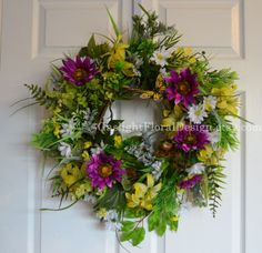 Passion Moon Sunflower & Tiger Lily Wreath  Add a pop of purple to your home decor. These interesting sunflowers and yellow tiger lilies are lovely among the daisies, dusty miller, and greenery. Passion Moon Sunflower wreath is accented with a sweet bird and bright butterfly. The base for this wreath is a grapevine and the dimensions are 25x25x9. $90.00