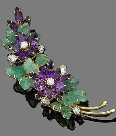 A carved emerald, amethyst and diamond spray brooch The flowerheads set with brilliant-cut diamonds and pear-shaped amethysts, within a surround of carved emerald leaves, diamonds approx. 2.00ct total, length 8.2cm