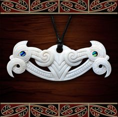 This pekapeka pendant, shaped like a pare (lintel), measures 32mm in height, 77mm wide and 5mm thick. Intricately detailed, it has a full manaia head at each end with Paua shell eyes.