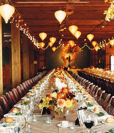 Love the paper lanterns hanging from the barn rafters, long tables and clean table settings.  Use of florals and leaf wreath in background make this perfect for event in the fall.
