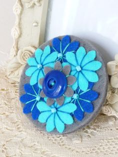 Grey with royal blue and turquoise flowers and button in center circular felt pin.