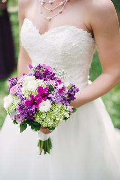 This bride complemented her organza and lace bridal gown with a pretty purple wedding bouquet. | Kennedy Blue