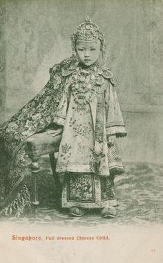 This postally-unused postcard shows a young Straits Chinese or nonya girl dressed for her role in a traditional Straits Chinese wedding. She has a long, finely beaded cloak trailing to her side, a Ching-style gown, and numerous items of jewellery including rings, and a head piece and chest ornaments based on the bride's sanggul kemantain and dada kemantain.